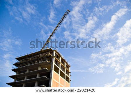 crane and building on sky with clouds
