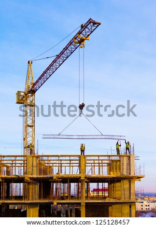 Crane and workers at  construction site against blue sky.