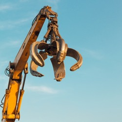 crane arm with open claw on clear blue sky