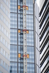 Crane attached to the wall of the building, crane anchoring, building construction in the center, big city