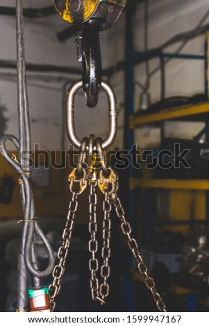 Crane chain in a factory workshop for lifting heavy objects. Working specialty at the factory.