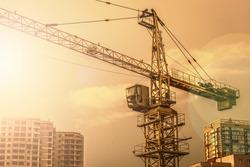 Crane. Construction crane. Building crane on the background of two buildings.
