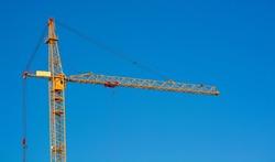 Crane. Construction crane. Huge crane against blue sky. Self-erection cranr. Tower crane.