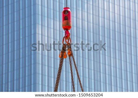 Crane hoisting block with hook on steel chain on steel rope. Glass facade of a modern skyscraper in the background. Loading\unloading of building materials on construction building site.