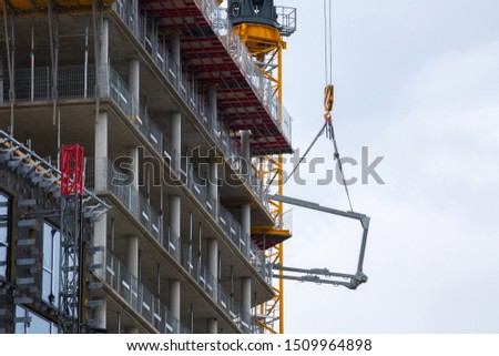 Crane hoisting block with hook on steel chain on the steel rope lift the huge steel beams. Loading\unloading of building materials on construction building site.