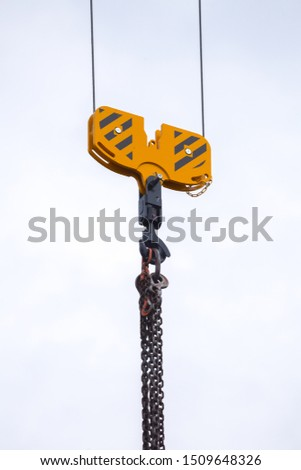 Crane hoisting block with hook on steel chain on the steel rope. Loading\unloading of building materials on construction building site.
