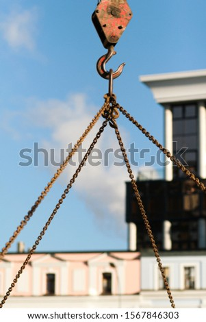 Crane hoisting heavy cargo with rusty metal hook on rusty chains. Buildings in the background in the city center