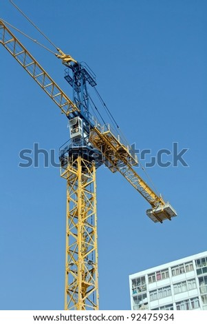 crane in action on a blue sky and building