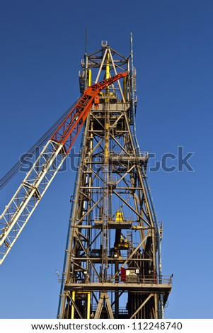 Crane in front of a derrick on an offshore drilling platform.