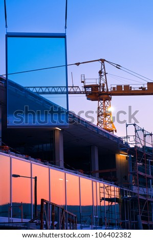 Crane installs a new glass panel on office building under construction - stock photo