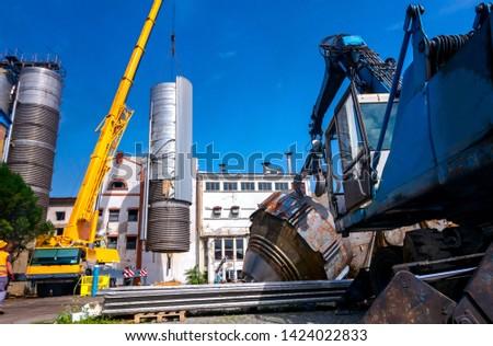Crane is bringing down heavy metal silo in industrial complex. Stock fotó ©