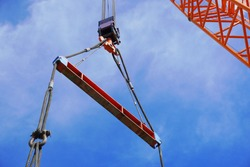 Crane is lifting the machine using spreader bar and sky background in a chemical factory.