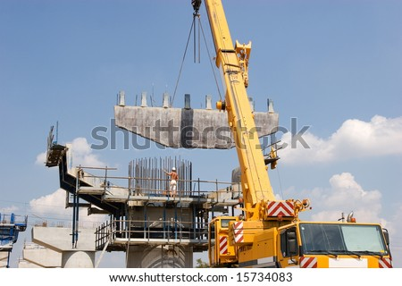 Crane lifting a metal frame to place it on pillar