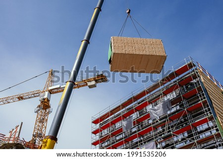 Crane lifting a wooden building module to its position in the structure. Construction site of an office building in Berlin. The new structure will be built in modular timber construction. Stockfoto ©
