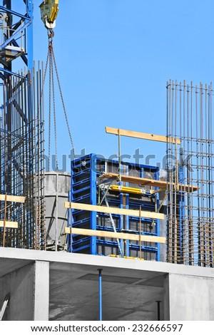 Crane lifting concrete mixer container against blue sky #232666597
