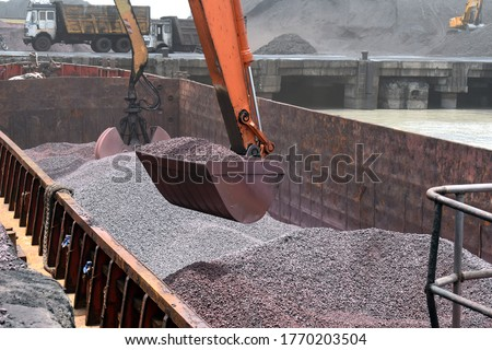 Crane Lifting Iron Ore From the Barge at Dindayal Port Kandla India. Iron Ore Imported from Australia. Big Hydraulic Grabs of Crane at work