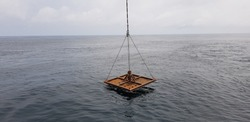 crane lifts a metal frame for subsea  construction