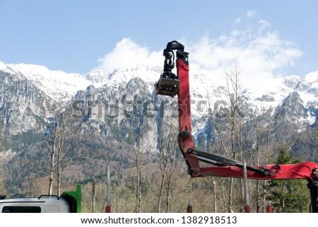 crane loads wood logs into the mountains #1382918513