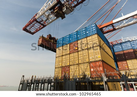 crane lowering container to stack of containers