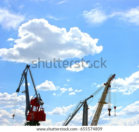 Crane on the river. Against a blue sky with clouds. Metal city construction  #655574809