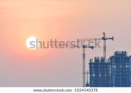 Crane on top of the building, sunset in the evening. #1024540378