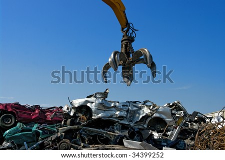 Crane picking up crushed cars