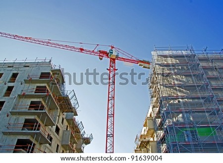 crane surrounded two buildings under construction, modernity in motion