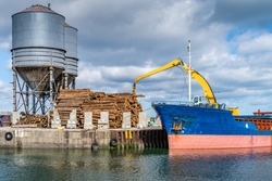 Crane with wood logs gripple loading timber on cargo ship for export in Wicklow commercial port. Transport industry in Ireland