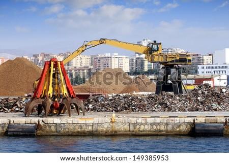 Crane working with scrap metal stored in port