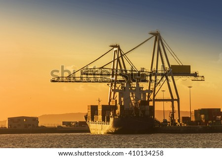 Cranes and container transport ship docked on Vilagarcia de Arousa harbor at sunset