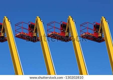 Cranes and hydraulic lifting platforms and a blue sky - stock photo
