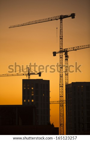 Cranes at sunset. Industrial construction cranes and building silhouettes over sun at sunrise. Vertical format