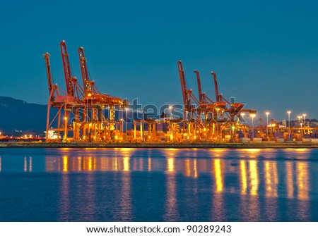 cranes at the container port terminal in Vancouver BC sunset time - stock photo