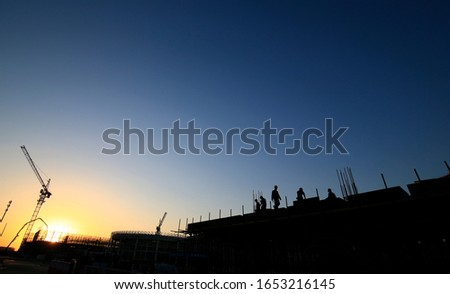Cranes at work, silhouetted on construction sites
