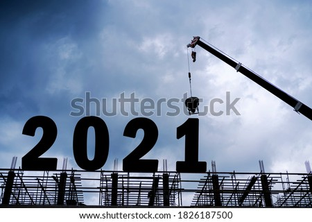 Cranes building construction 2021year sign,Silhouette staff works as a team to prepare to welcome the new year 2021