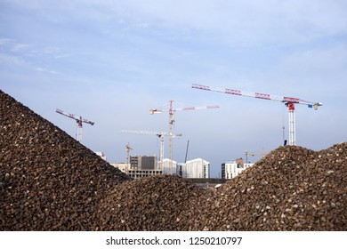 Stock photo of cranes at construction site, behind piles of gravel.