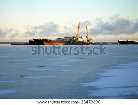 Cranes in dockside before the sunset on a frozen lake - industrial landscape