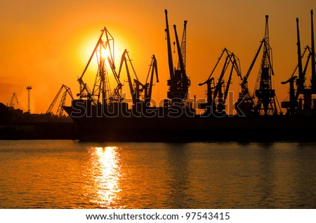 Cranes in the harbor against a sunset