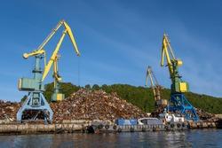 Cranes loading scrap metal In port