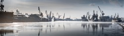 Cranes of of the Baltic shipyard on a frosty winter day, steam over the Neva river, smooth surface of the river, mirror reflection on the water, ships under construction, trawlers, nuclear icebreakers