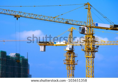 Cranes on construction site under blue sky