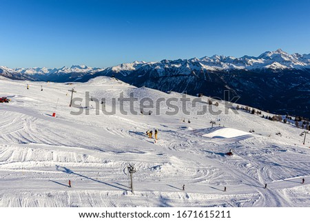 Crans-Montana Ski Resort taken from a distance with snowy mountains on the horizon and the snow park in the foreground, featuring a chair lift, tow rope, and snow groomers Photo stock ©