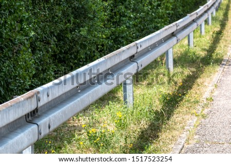 Crash barrier by the street with bushes, grass and asphalt #1517523254