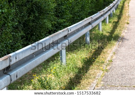 Crash barrier by the street with bushes, grass and asphalt #1517533682