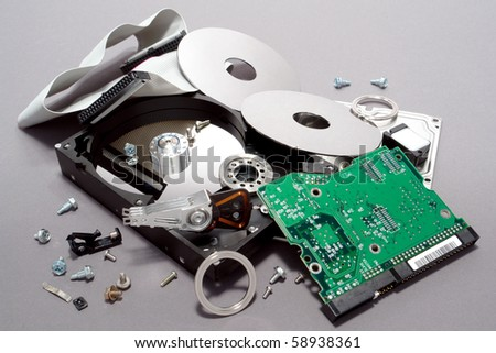 Crashed and broken apart dismantled computer hard drive with scattered component parts showing loose disks and circuit board with spread out assembly hardware