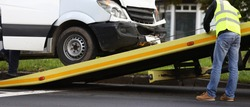 Crashed minibus is loaded onto tow truck after an accident. Evacuation and towing services concept