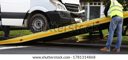 Crashed minibus is loaded onto tow truck after an accident. Evacuation and towing services concept Foto stock ©