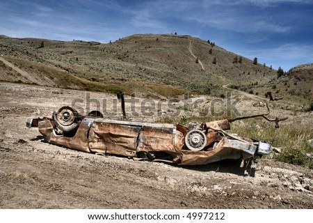 Crashed, rusty car in desert. Photo taken near Kamloops, British Columbia, Canada (North America).