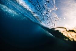 Crashing surfing wave in ocean with warm tones at sunrise or sunset. Split shot