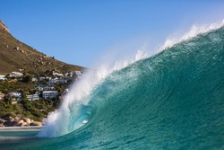 crashing wave with lions head in the background in cape town , south africa